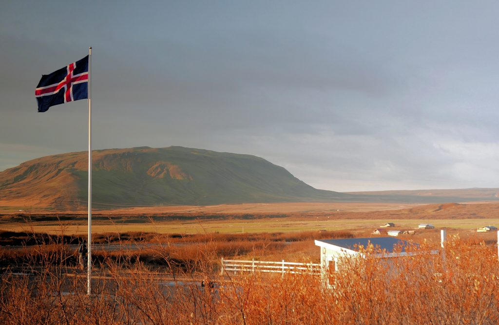 Iceland flag and hilly landscape, Iceland on a budget