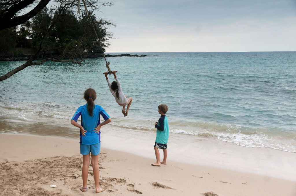 kids swinging on the beach in Hawaii family gap year