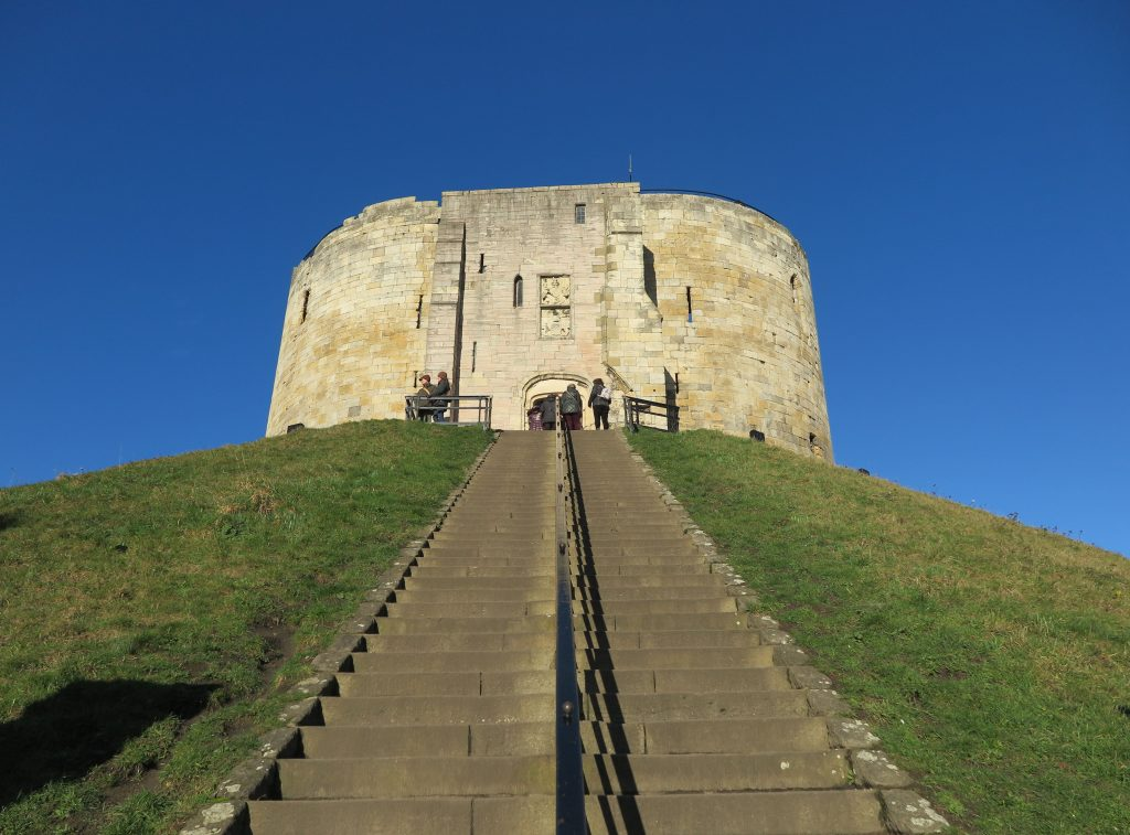 a round stone tower on a green hill against blue sky, stone steps lead up to the tower