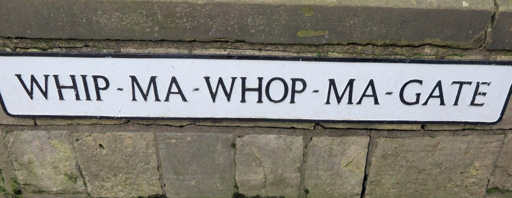 A street sign in York, Whip Ma Whop Ma Gate, black lettering on white background, York with kids