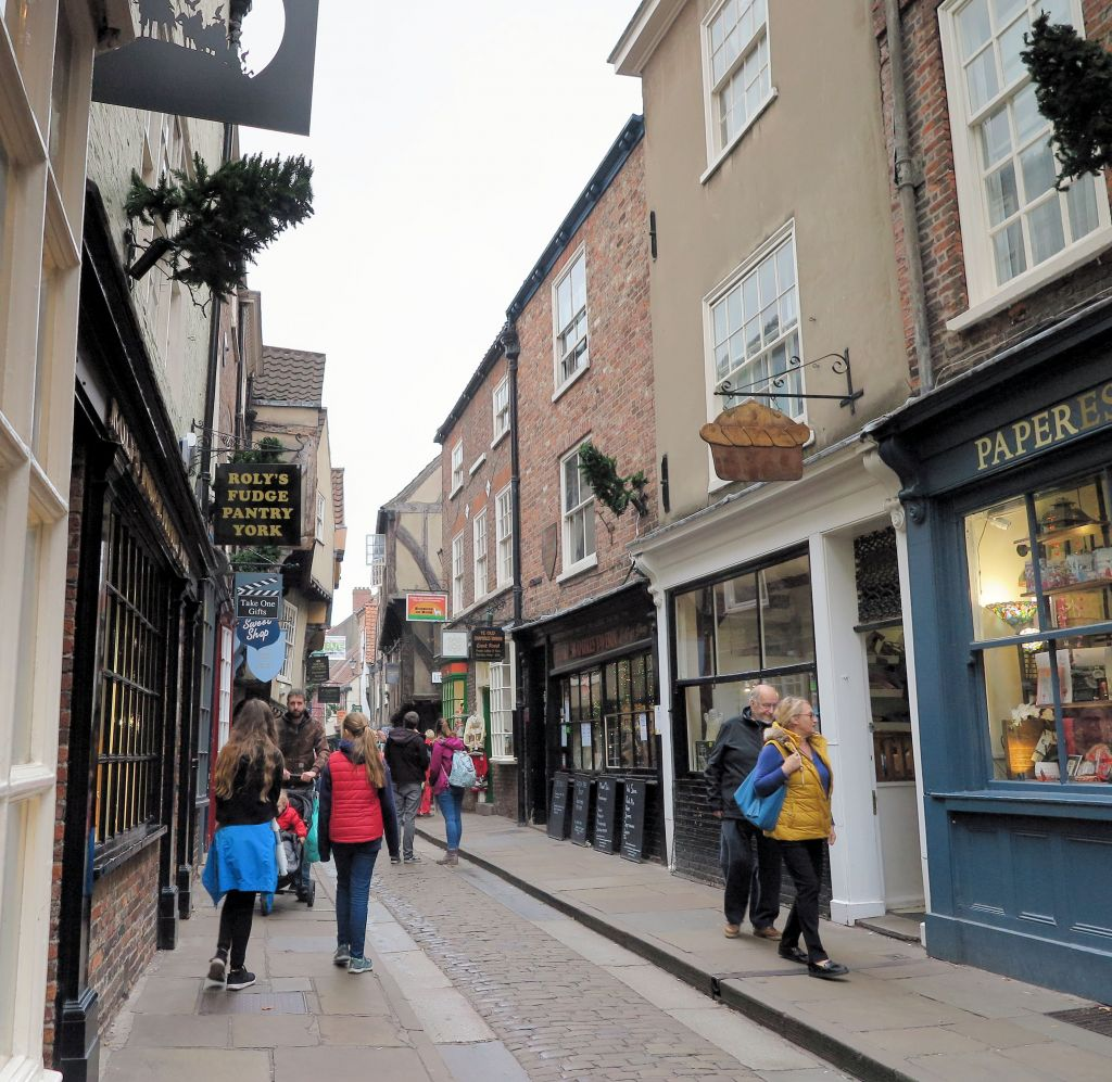 people walking on a cobbled street under overhanging medieval buildings