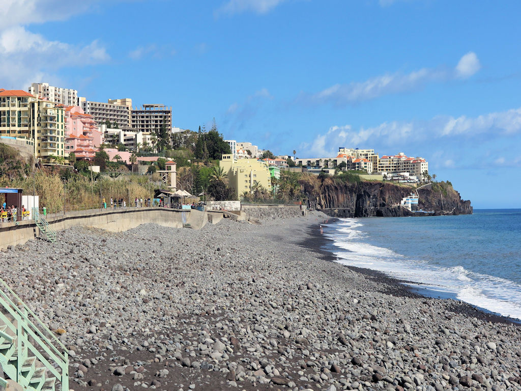 grey sandy and rocky beach lined with big hotels overlooking the sea, hiking in Madeira