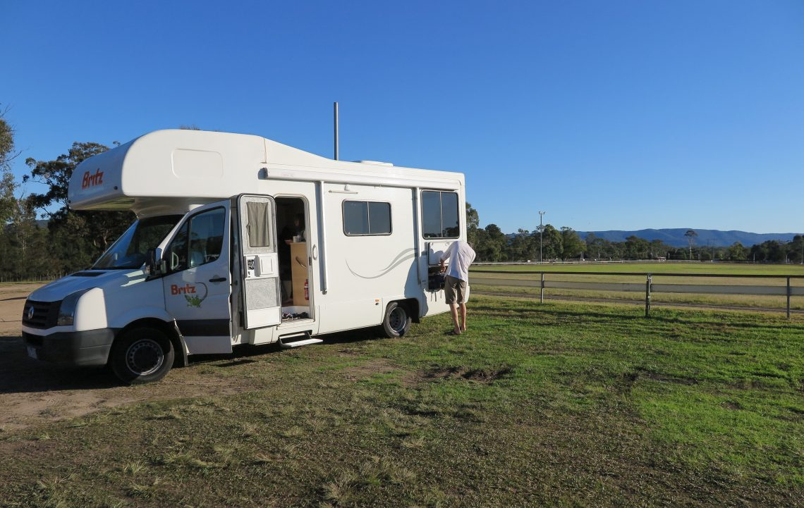 white Britz motorhome on a green field camp site, blue ksy