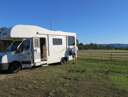 white Britz motorhome on a green field camp site, blue ksy