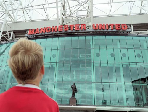 boy standing in front of glass windows at Man Utd football stadium