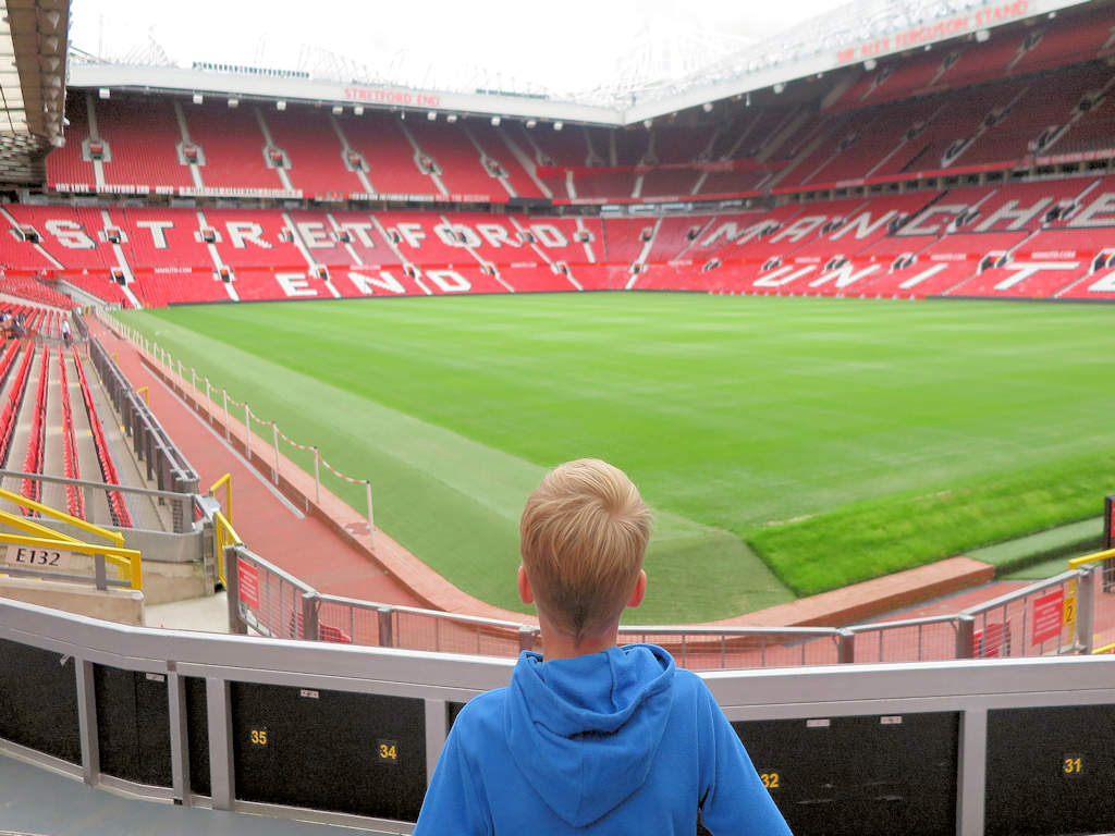 boy looking at pitch and stands at Manchester United Stadium tour