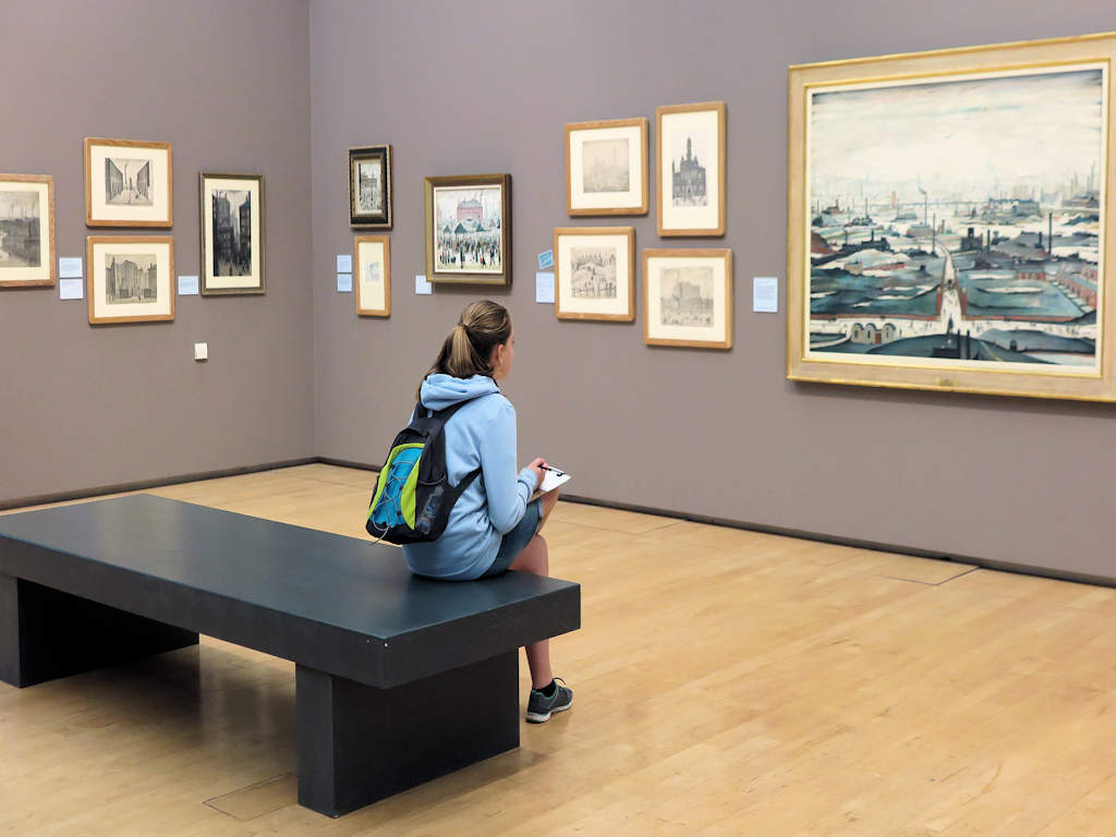 girl sitting in front of paintings at the Lowry Art Gallery Manchester