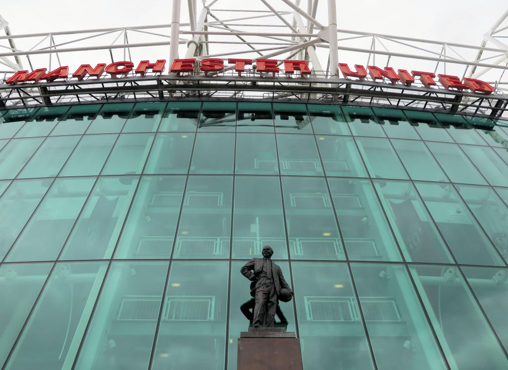 glass front and statue outside Old Trafford football stadium