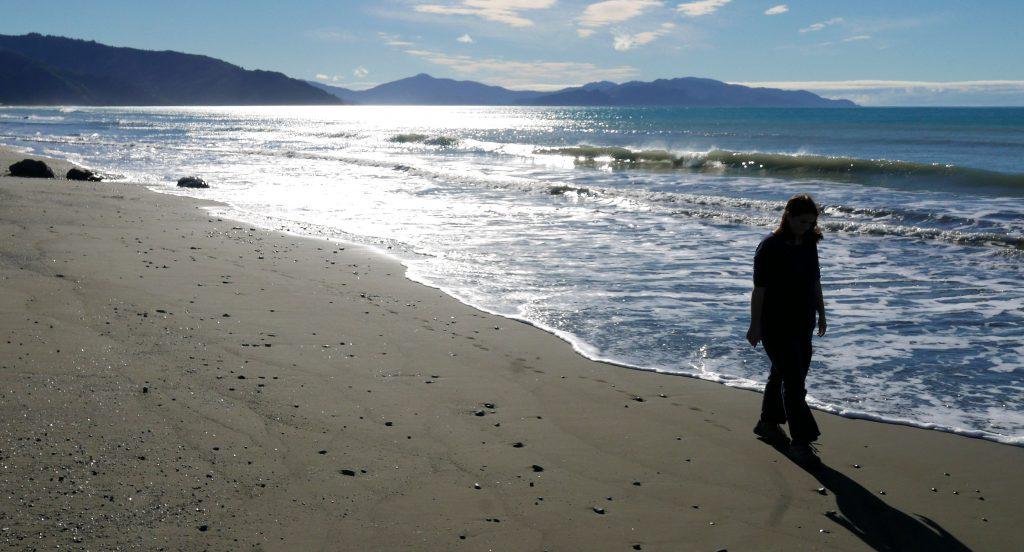 woman walking on a beach Campervan road trip New Zealand