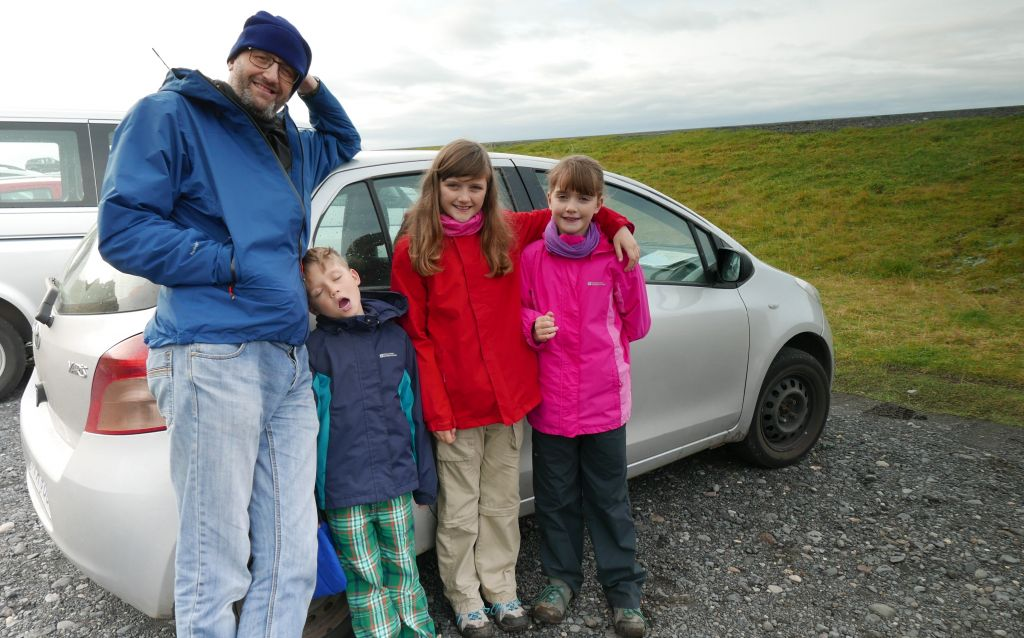 family standing in front of car, budget trip to Iceland