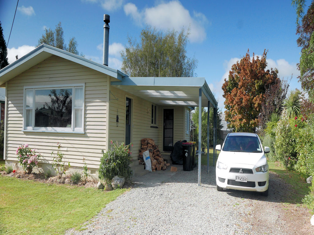 cream slat wooden house with white care, best Airbnb in New Zealand