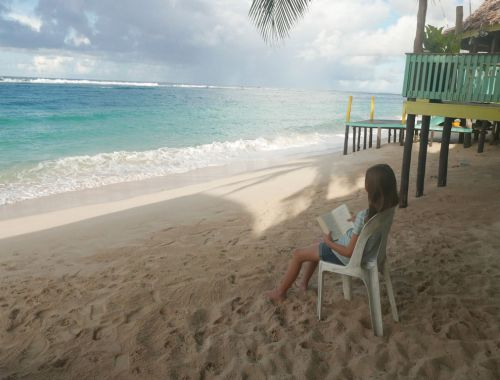 girl reading a book on the beach Samoa with kids family gap year