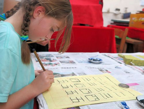 girl learning chinese writing, homeschooling while travelling