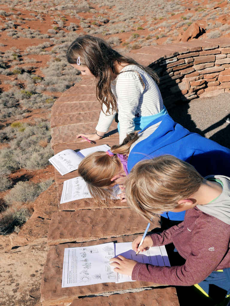 children writing, homeschooling while travelling