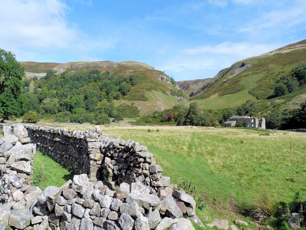 dry stone wall and hiking path through a green field things to do with kids in Yorkshire