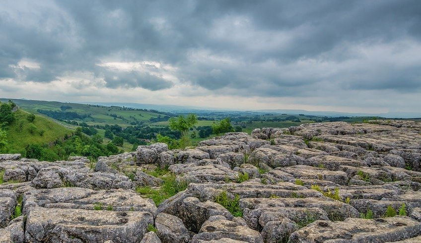 Grey limestone pavement at Malham Cove, gree trees and grey cloudy sky