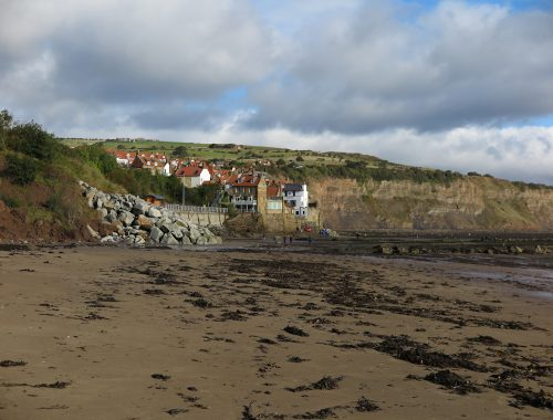 sandy beach with seaweed, white houses in distnace, things to do on the yorkshire coast