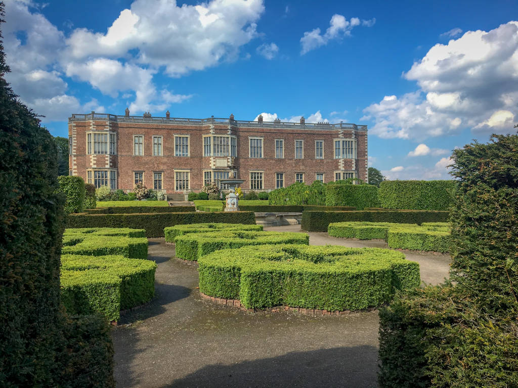 brown brick stately home against blue sky with green hedges in front