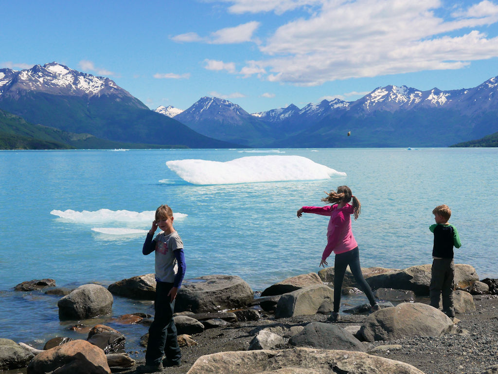children throwing stones inot a lake with mini icebergs Argentina with kids
