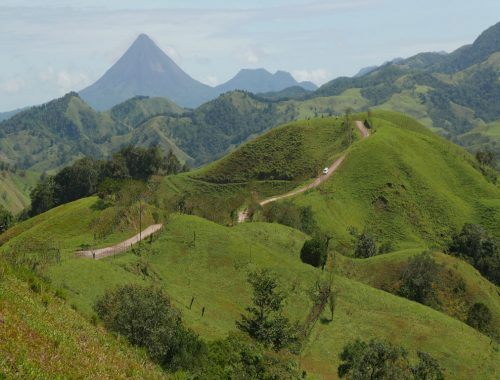 green hils with a brown path through it, conical volcano in background Costa Rica itinerary 10 days