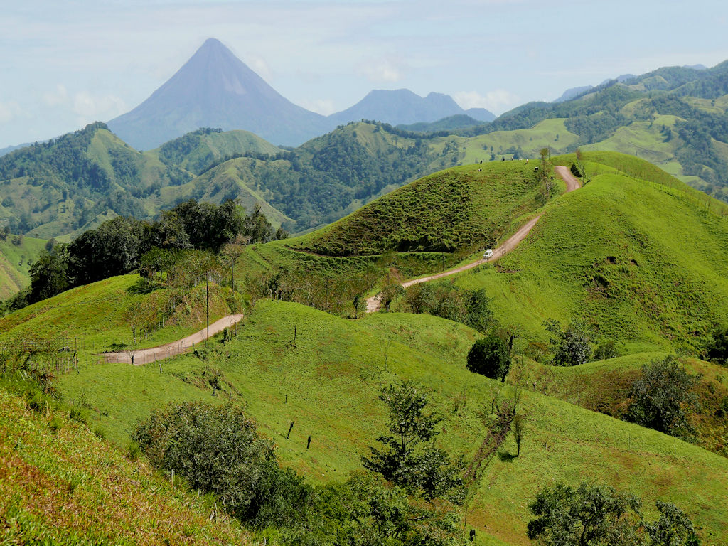 green hills and fields with distant cone volcano, Arenal Costa Rica