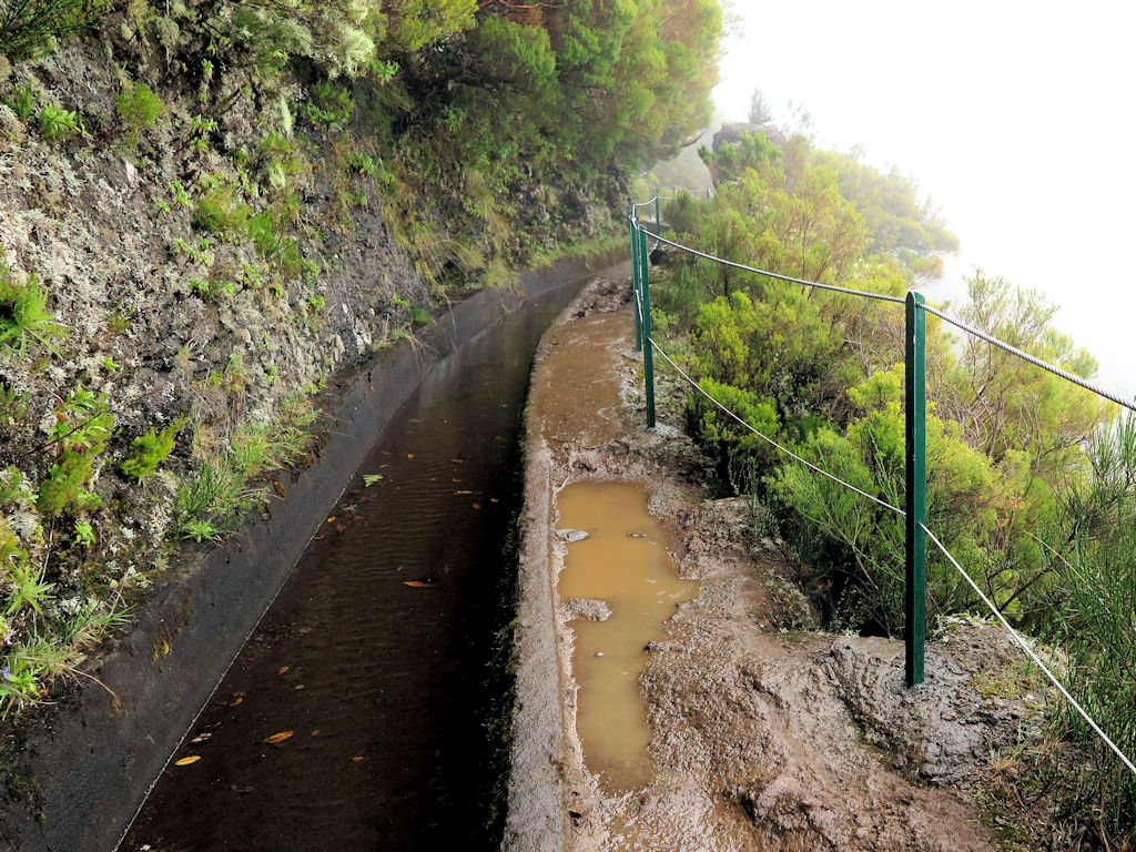 irrigation channel next to a muddy path with a rickety fence and green bushes, Madeira hiking tips