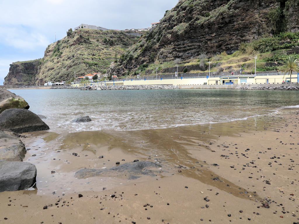 yellow sand beach against calm sea water and green cliffs in background, beaches in Madeira