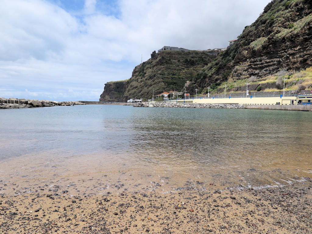 yellow sand with small rocks, calm sea water, against promenade and cliffs, best beaches in Madeira,