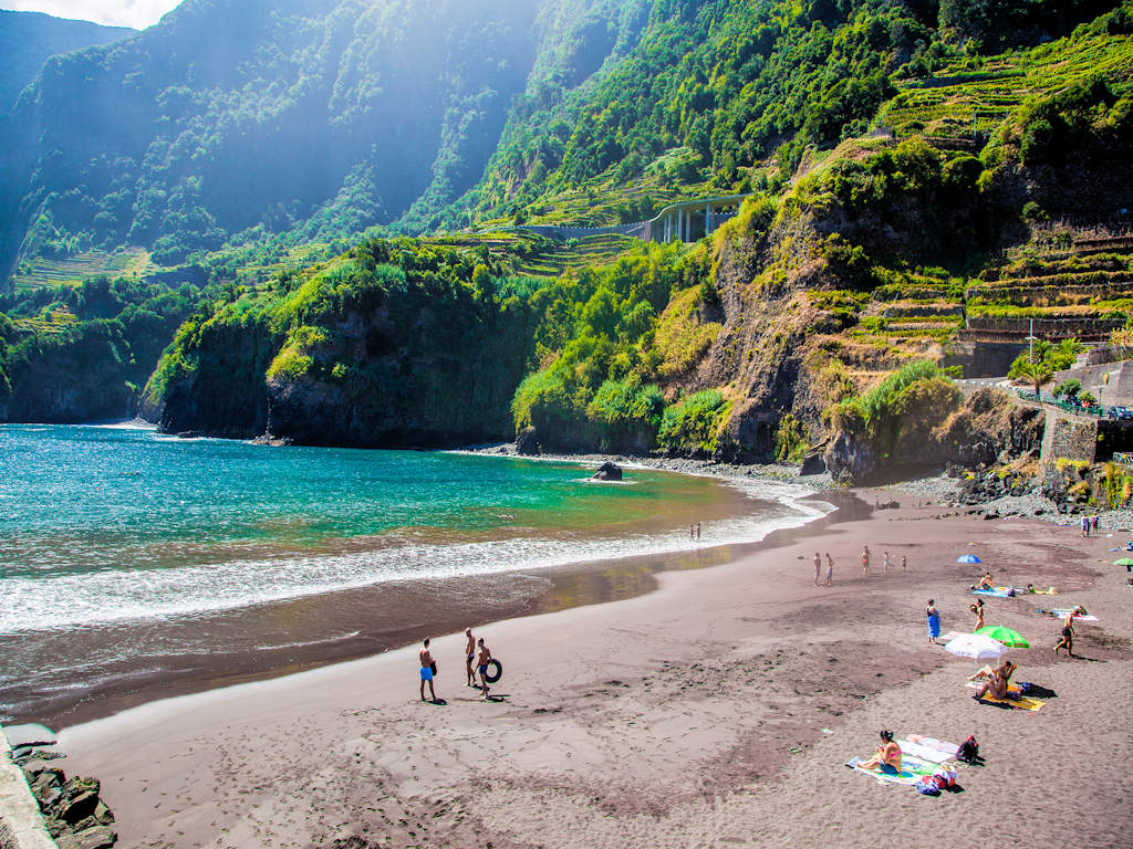volcanic sand beach against blue water and green sea cliffs