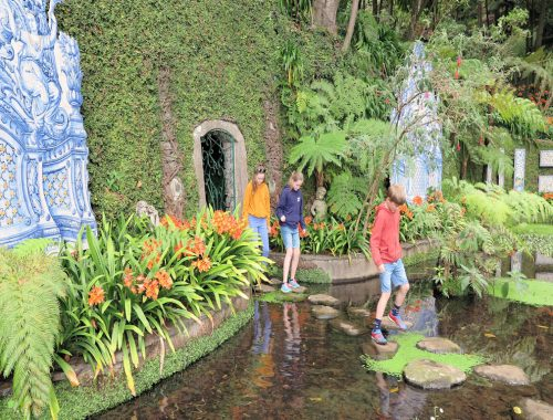 three children on stepping stones over a pond in a lush green park, Madeira Family holiday