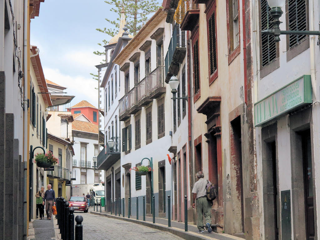 cream and ornage old buildings with balconies, naroow car less street, Madeira family holiday