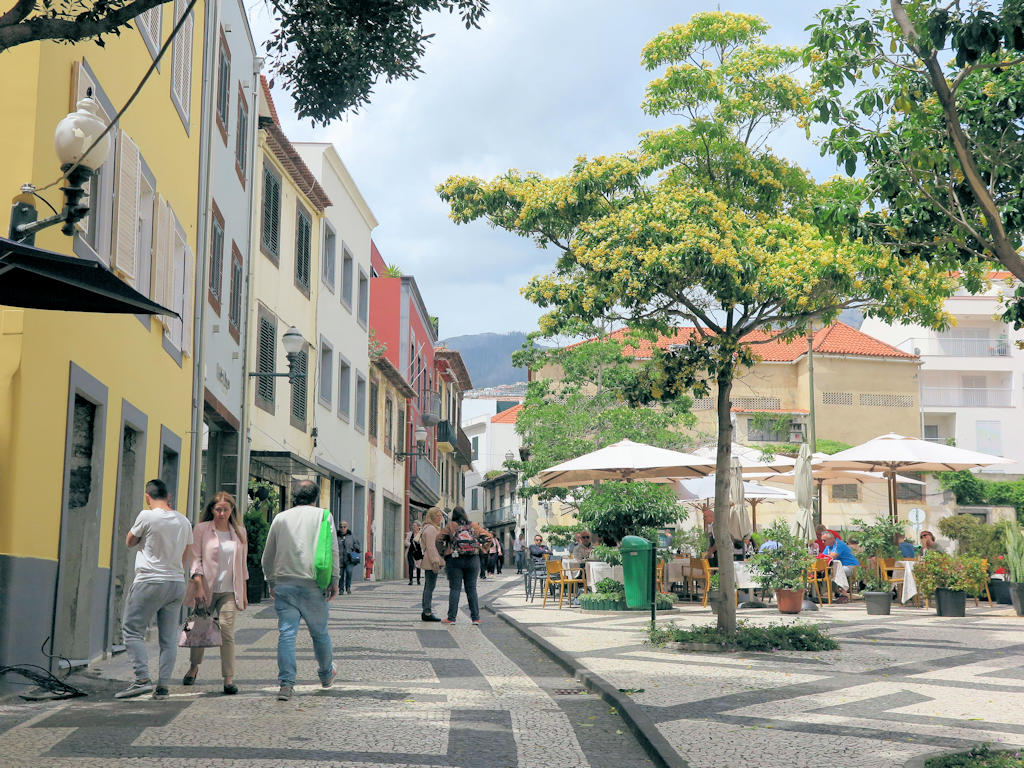 people walking on a black and white pavement wurrounded by tall pastel coloured buildings, Funchal Madeira