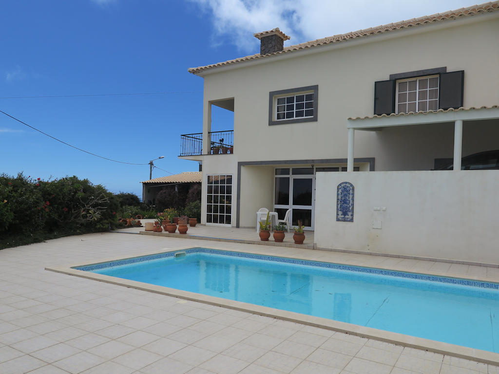 whitewashed villa against blue sky, blue swimming pool on the ground, villas in Madeira